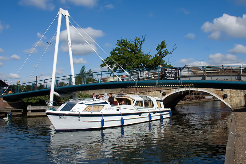 A cruiser navigating Wroxham Bridge on the River Bure